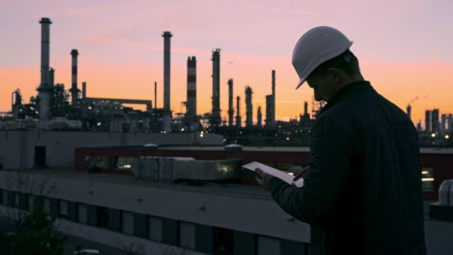 stockvideo's en b-roll-footage met ms mannelijke ingenieur in hardhat die digitale tablet op raffinaderijdak bij schemering gebruikt - olieraffinaderij