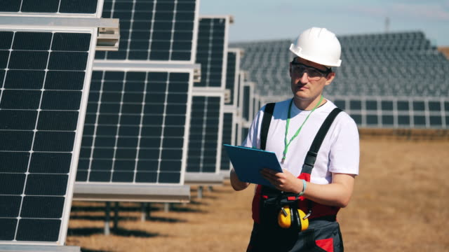 Male engineer is checking solar batteries. Renewable energy, solar plant, green electricity concept. Male engineer is checking solar batteries. 4K power supply stock videos & royalty-free footage