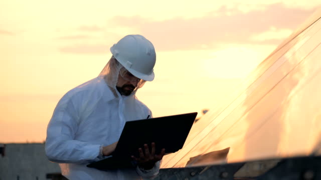 Male engineer is observing a solar construction and working with a laptop
