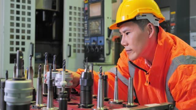工場フロアでcnc機械を操作する男性エンジニア - オペレーター 日本人点の映像素材/bロール