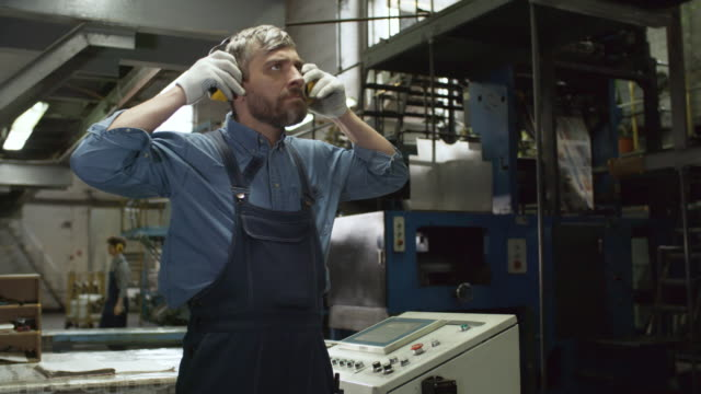 Male Engineer Operating Industrial Machine in Factory Panning shot of middle aged Caucasian male technician putting on safety ear muffs, looking at industrial machine and pressing buttons on operating console while working in factory ear stock videos & royalty-free footage
