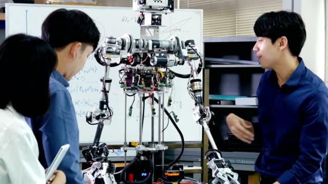 vídeos de stock, filmes e b-roll de projeto de engenheiro masculino presente com equipe. engenheiro da equipe começar para projeto de robô juntos. pessoas com o conceito de tecnologia ou inovação. resolução de 4k. - nova empresa