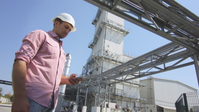 Male engineer speaking phone on chemical factory background video