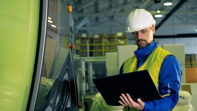 Male engineer types on a laptop, standing in a facility, factory equipment. Male engineer types on a laptop, standing in a facility, factory equipment. 4K business symbols stock videos & royalty-free footage