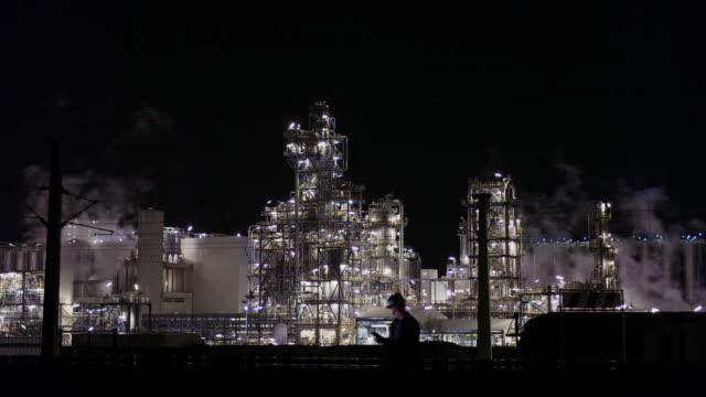 stockvideo's en b-roll-footage met ws mannelijke ingenieur die digitale tablet bij verlichte olieraffinaderij bij nacht gebruikt - raffinaderij