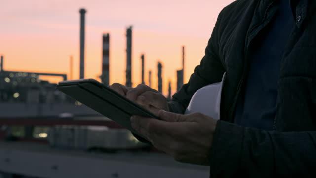 stockvideo's en b-roll-footage met cu mannelijke ingenieur die digitale tablet bij raffinaderij bij schemering gebruikt - chemische fabriek