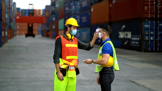 Male Engineer Wearing Protective Face Mask And Spraying Alcohol To Worker's Hand Before Start Working In A Commercial Shipping Dock During Coronavirus Crisis