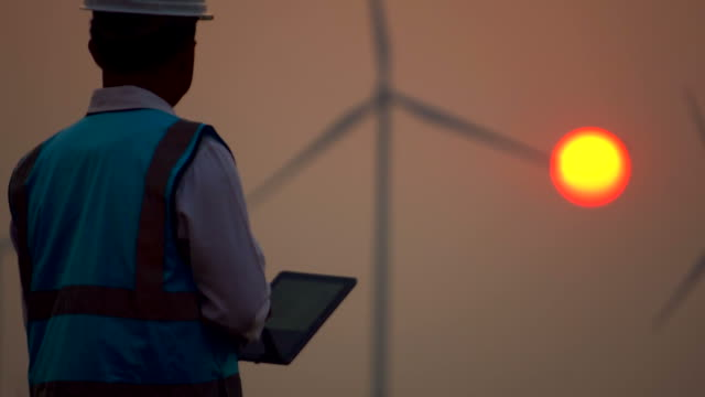 male engineer with digital tablet in front of wind turbines - turbina a vento video stock e b–roll