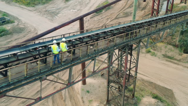 Male engineers are walking along the railing in port video