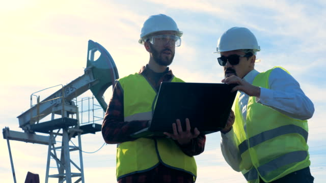 Male engineers work with a laptop on an oilfield, close up.