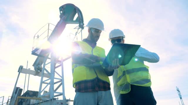 vídeos de stock, filmes e b-roll de coordenadores masculinos que trabalham em um campo petrolífero perto das bombas de petróleo. - gasolina