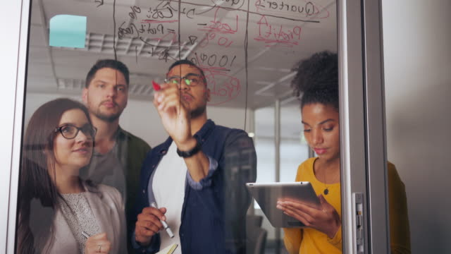 Male entrepreneur discussing business ideas and plans on a glass board with his colleague in office Business colleagues working on new project together in office blackboard visual aid stock videos & royalty-free footage