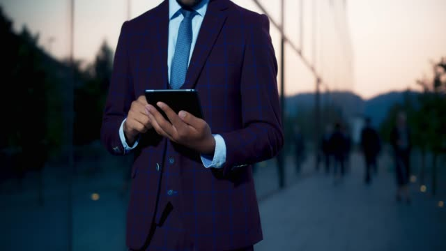 Video Male entrepreneur in a quirky business suit standing outside a modern business building and typing on the digital tablet