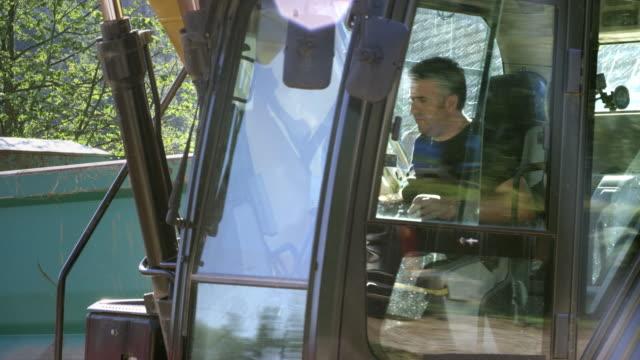 manliga grävmaskin operatör arbetar på en byggarbetsplats - excavator bildbanksvideor och videomaterial från bakom kulisserna