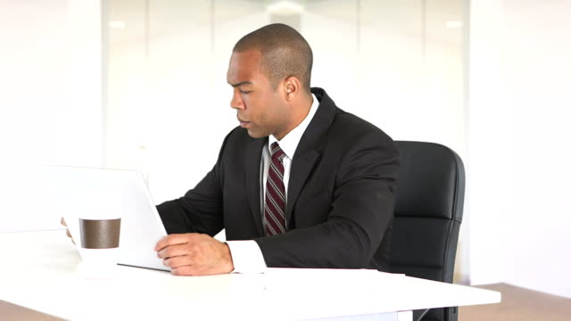 Male executive at desk with laptop and cell phone video
