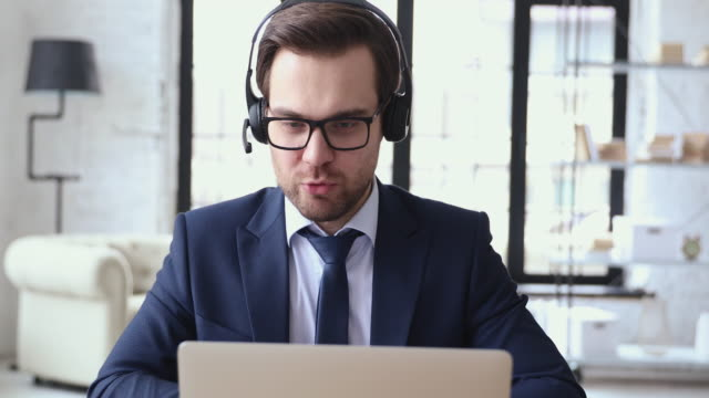 Male executive wears headset video calling by webcam on laptop Male executive wears headset video calling on laptop. Businessman webinar speaker streaming live web training. Call center agent, service support manager speaking to distance customer in webcam chat. conference call stock videos & royalty-free footage