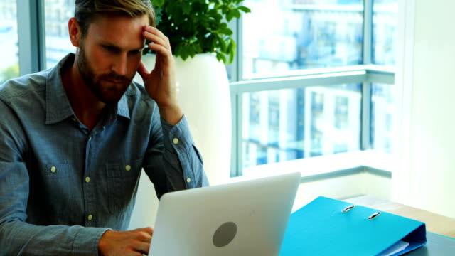 Mâle exécutif travaille sur ordinateur portable au bureau - Vidéo