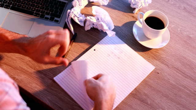 Male executive writing on paper at his desk 4k video