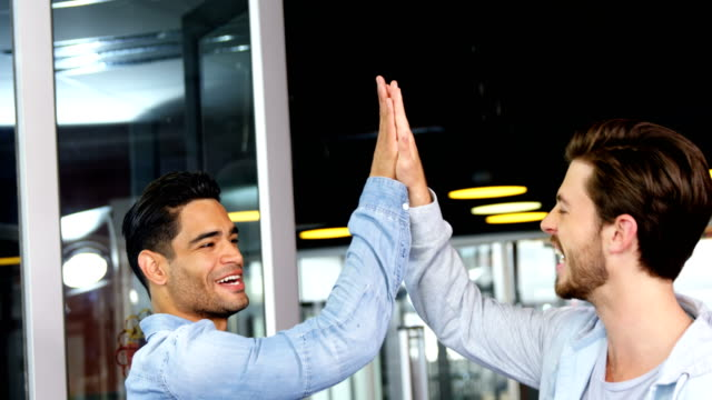 Male executives giving high-five to each other video