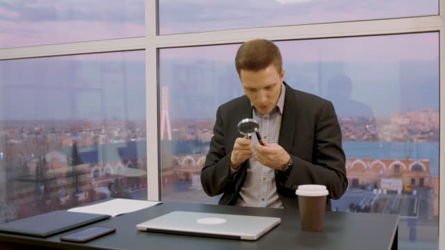 male expert checking pen with magnifying glass while sitting at workplace - expert стоковые видео и кадры b-roll