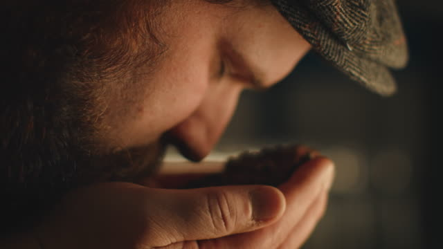 Male expertise smelling roasted coffee beans