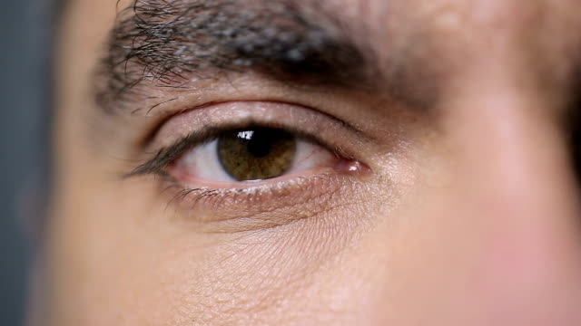 male eye looking into camera, closeup shot. eye exam, vision care, ophthalmology - vicino video stock e b–roll