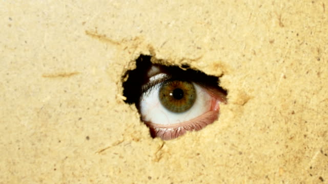 male eye looking through hole in wall - dziura filmów i materiałów b-roll