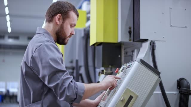 プログラミング用コンソールを使用してcncマシンを操作する男性工場従業員 - 機械部品点の映像素材/bロール