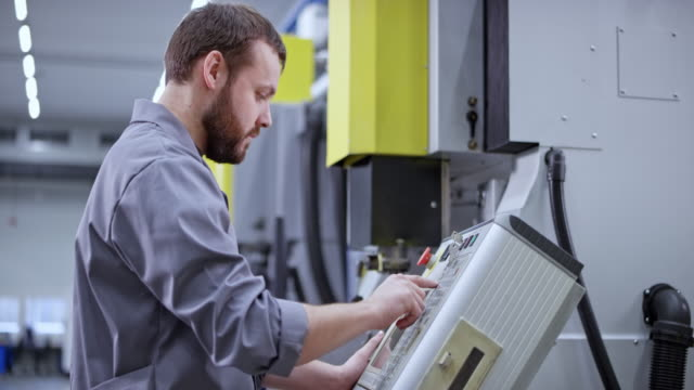 vídeos de stock e filmes b-roll de male factory employee operating a cnc machine using a console for programming - mecânico