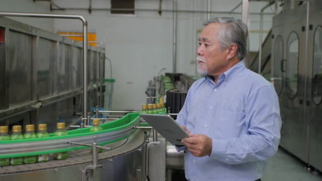 a male factory manager in beverages manufacturing industry looking at computer tablet and checking the quality of the product. production of drinking water and beverages - esaminare video stock e b–roll