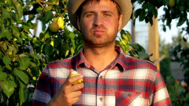 Male Farmer Eats A Ripe Pear On A Background Of Fruity Garden