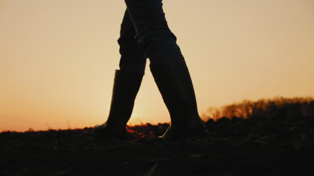 Male farmer in rubber boots walking through cultivated agricultural field