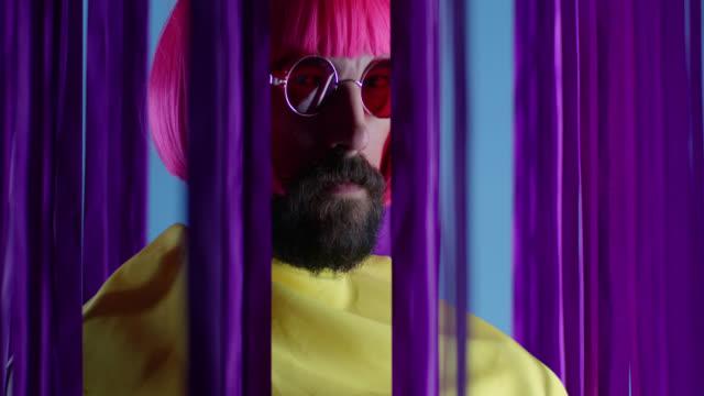erkek moda model pembe peruk ve güneş gözlüğü, sarı bir palto giyiyor. moda video. - peruk stok videoları ve detay görüntü çekimi