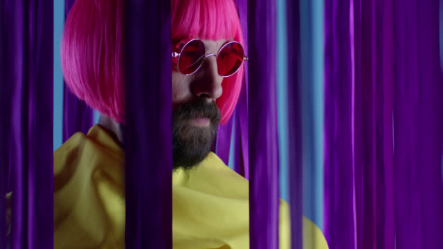 Male fashion model in pink wig and sunglasses, wearing yellow coat. Fashion video. Male fashion model in pink wig and sunglasses, wearing yellow coat. Fashion video. Slow Motion. 4K 30fps ProRes 4444 performer stock videos & royalty-free footage