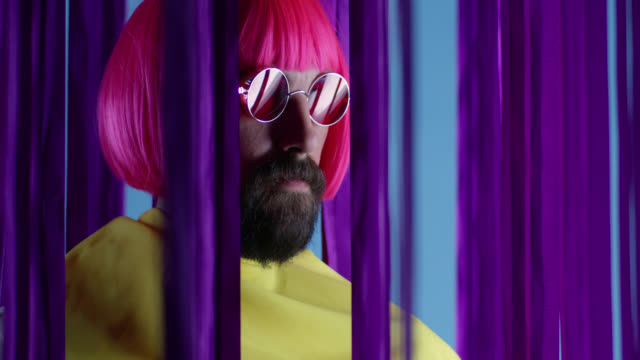 Male fashion model in pink wig and sunglasses, wearing yellow coat. Fashion video. Male fashion model in pink wig and sunglasses, wearing yellow coat. Fashion video. Slow Motion. 4K 30fps ProRes 4444 supermodel stock videos & royalty-free footage