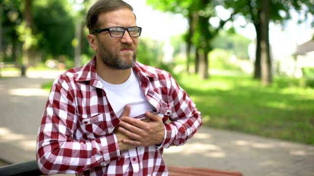 vídeos de stock e filmes b-roll de male feeling chest pain, sitting outdoors, heart arrhythmia, ischemic disease - sistema cardiovascular