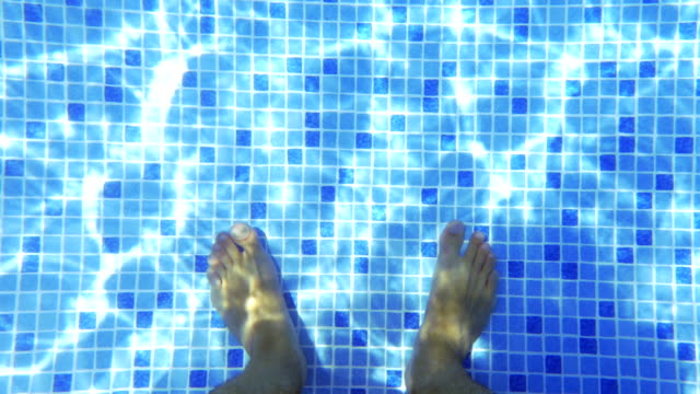 Male feet in clear water of the pool video