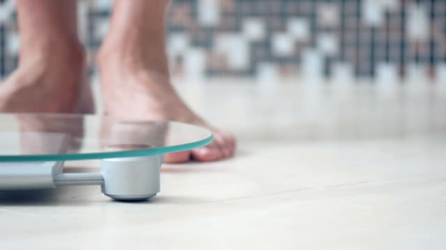 Male Feet Standing On Electronic Scales For Weight Control On The Bathroom Closeup Stock More Clips Of 1018242016 Istock