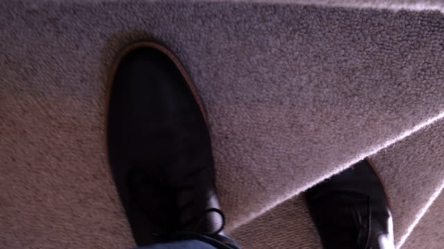 Male feet walking upstairs. Personal perspective. Personal perspective view lowlight shot of a man walking upstairs. 60fps SM. staircases stock videos & royalty-free footage