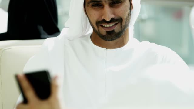 Male female Arabic travellers drinking coffee hotel lobby video