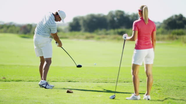 Male female Caucasian golfing couple playing on fairway video