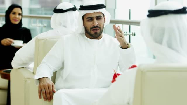 Male female Emirati travellers drinking coffee hotel lobby video