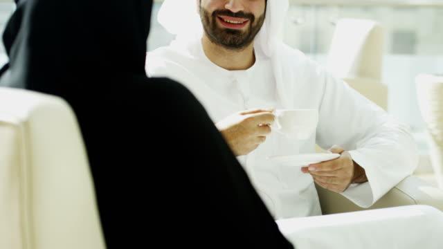 Male female Emirati travellers drinking coffee international hotel video