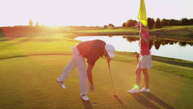 Male female golfing partners preparing the final putt video
