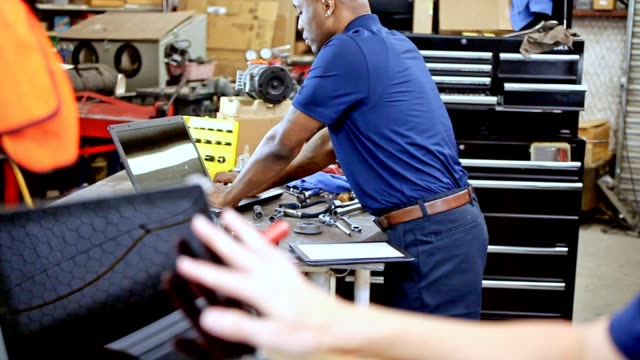 Male, female mechanics working together in auto repair shop. video
