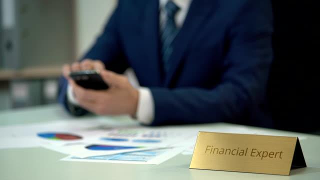 мужской финансовый эксперт с помощью смартфона, просмотр бизнес-документов с диаграммами - expert стоковые видео и кадры b-roll