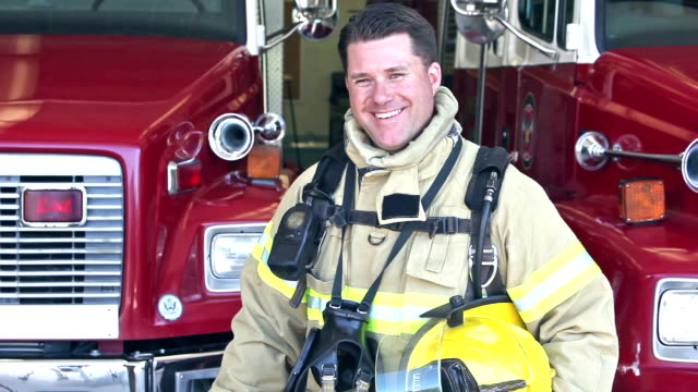 male firefighter standing in front of fire engines - firefighter stock videos and b-roll footage