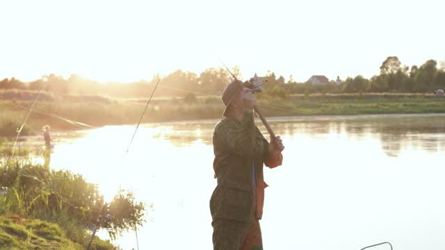male fisherman actively fishing on the lake. - żabnicokształtne filmów i materiałów b-roll