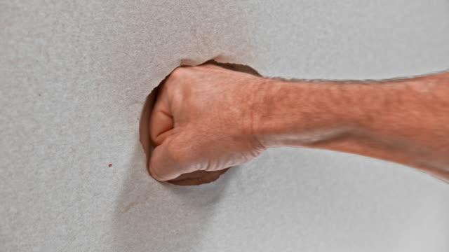 vídeos de stock e filmes b-roll de slo mo ld male fist punching through drywall - dar murros