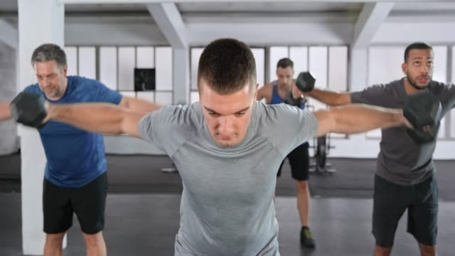Male fitness instructor leading a male class working out with weights in the fitness center Wide handheld shot of a male Caucasian instructor leading a small all male class working out with weights. Shot in Slovenia. handsome people stock videos & royalty-free footage